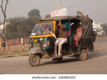 Delhi, India - 2/20/2011:  A fully loaded tuc tuc taxi on a main street in Delhi.