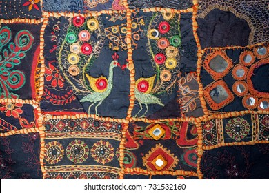 DELHI, INDIA - 5 OCT: Vintage homemade patchwork with ethnic details, birds and floral patterns on texture of old blanket on 5 October, 2017. Cotton was domesticated in India by 4000 BCE.
