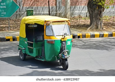 DELHI, INDIA - 8 APR 2017 : An auto rickshaw in Delhi, India  also known as  tuk-tuk in Thailand. Most have three wheels and yellow - green color.