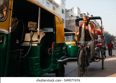 DELHI, INDIA - 9 MARCH 2013: A Rickshaw driver rides behind a auto-rickshaw in Paharganj, Delhi. Delhi is the 2nd most populous city in India behind Mumbai.