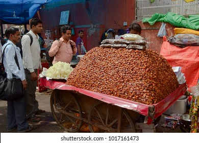 Delhi, India - April, 2014: Big heap of dry dates fruits on a wooden cart on wheels . Man selling sweet foods on the street market stall