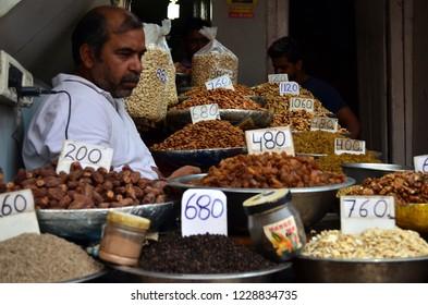 Delhi, India, circa 2018. Shopkeeper selling dry fruits (walnuts, dates, cashews, raisins etc) in Khari Bouli, Fatehpuri, Chandni Chowk, Old Delhi, the biggest wholesale market for Dry Fruits in Delhi