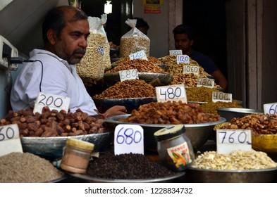 Delhi, India, circa 2018.Shopkeeper selling dry fruits (walnuts, dates, cashews, raisins, almonds) in Khari Bouli, Fatehpuri, Chandni Chowk,Delhi, the biggest wholesale market for dry fruits in Delhi