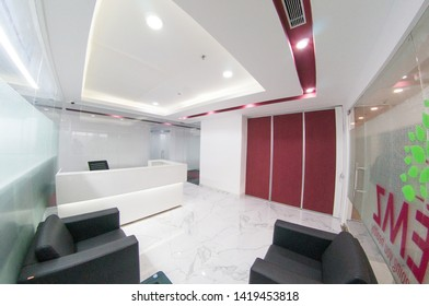 Delhi, India - Circa 2019 : fisheye shot of reception lobby for a modern office with white wallsand red inserts. The contemprory lighting and look make this a perfect image for a starup office