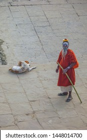 Delhi, India - DEC 11, 2011: old priest painted in the face in traditional manner with bamboo stick and sleeping dog. The red dress symbolizes his religious rule.