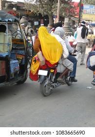 DELHI, INDIA - DEC 8, 2009 - Women in sarees ride side saddle on motorbikes through heavy urban trafficon Dec 8, 2009, in Fatepuhr Sikri, India.