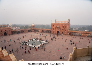 Delhi, India - December 04, 2019: Square with people and entrance gates infront of Jama Masjid.