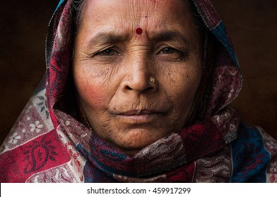 DELHI, INDIA - DECEMBER 22, 2015: Portrait of proud and fabulous indian old woman with bindi on her forehead and red headscarf, with eyes watching at the camera