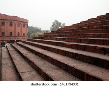 Delhi / India - February, 2nd, 2019: stairs leading to the Jama Masjid mosque entrance (one of). Very old and very large staircase of dark red color. No people. Poor visibility due to air pollution.