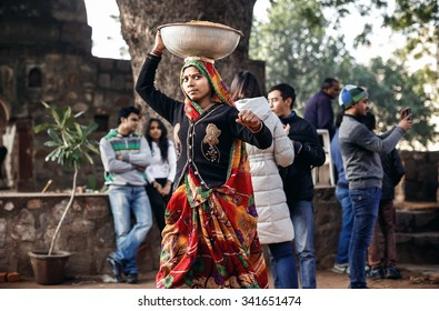 DELHI, INDIA - JANUARY 4, 2015: Indian young woman carrying big bowl on head on January 4, 2015 in Delhi, India