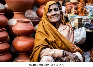DELHI, INDIA - JANUARY 4, 2015: Indian woman selling clay pots on local market  on January 4, 2015 in Delhi, India