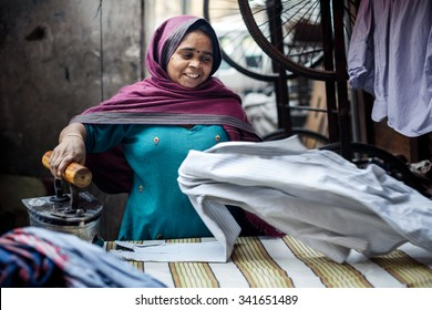 DELHI, INDIA - JANUARY 4, 2015: Mature Indian woman ironing clothes on January 4, 2015 in Delhi, India