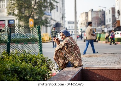 DELHI, INDIA - JANUARY 4, 2015: Young Indian woman sitting on the street on January 4, 2015 in Delhi, India