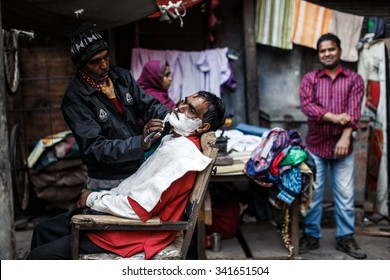 DELHI, INDIA - JANUARY 4, 2015: Barber shaving man on January 4, 2015 in Delhi, India