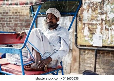 DELHI, INDIA - JANUARY 5, 2015: Indian man sitting in rickshaw cab on January 5, 2015 in Delhi, India