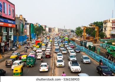 DELHI, INDIA - JULY 5, 2016: Heavy car traffic in the city center of Delhi, India. Buses and construction nearby the road. Various shops, cafes, restaurants.
