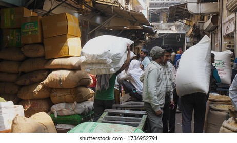 DELHI, INDIA - MARCH 14, 2019: porters carrying bags of spices at the spice market at chandni chowk