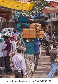 DELHI, INDIA - MARCH 28, 2014: A team of porters carry goods aloft through a bazaar in the heart of the city. The transportation of goods in this way is common in Indian towns