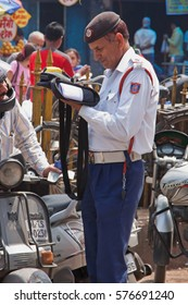 DELHI, INDIA - MARCH 28, 2014: A traffic policeman issues a ticket for a motoring violation in the busy Chandi Chowk area of the city. Traffic congestion is common in India's towns and cities