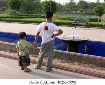 Delhi, India - May 01 2006: two boys of different age standing hand in hand watching a small fountain at gandhi samadhi area (backside view)