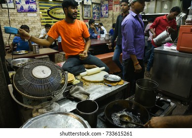DELHI, INDIA - MAY 12: Street food shop at Chandni Chowk. Man making paratha and people enjoying eating at restaurant at night on May 12, 2017 Old Delhi, North India.