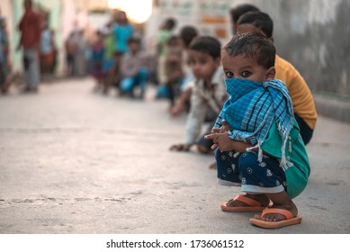 Delhi, India - May 17 2020: Poor children waiting in line for food distributed by a charitable trust in Delhi.