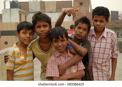 DELHI, INDIA - NOV 17, 2015: Unknown group of boys on a house roof. The kids are enthusiastic about the camera and joke around.