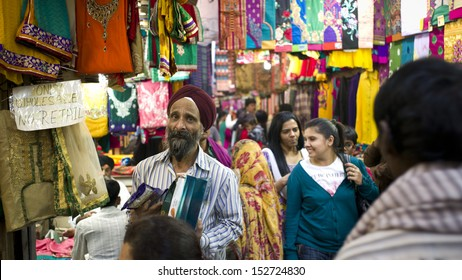 DELHI, INDIA - NOV 18: Unidentified shopkeeper sells blanket in a classical street in Old Delhi. November 18, 2012 in Delhi, India. India is famous for the colorful blankets.