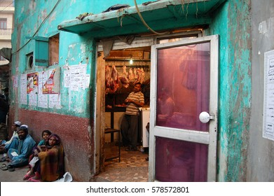 DELHI, INDIA - NOV 30, 2016: Unknown group of people in the muslim part of Delhi. The People are sitting in front of an store and looks curious into the Camera. In the store they sell fresh meat.