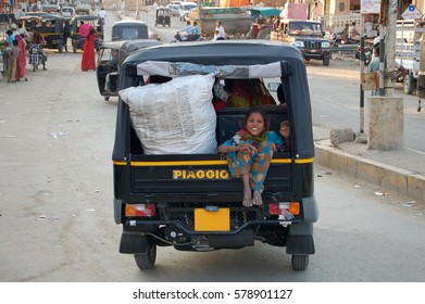 DELHI, INDIA - NOV 30, 2016: Unknown girl in the streets of Delhi. The girl is sitting at the backside of a tricycle and looks curious and happy into the Camera.
