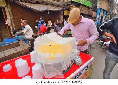 Delhi, India - November 20, 2017: A man selling daulat ki chaat, a local sweet dessert by the roadside.