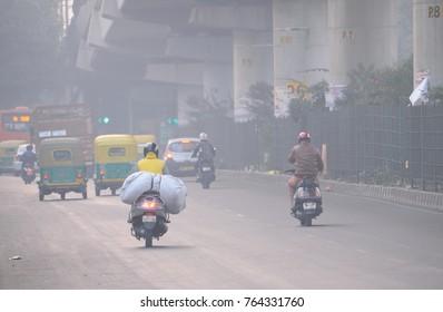 Delhi, India - November 21, 2017: Vehicles moving in the road amidst heavy smog.