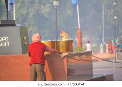 Delhi, India - November 21, 2017: A labor cleaning the Amar Jawan Jyoti in India gate.
