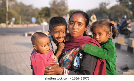 Delhi, India - November 28, 2018: Portraits of children and mothers working and begging on the streets of Delhi.