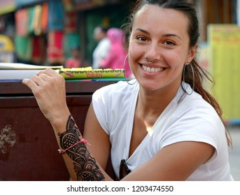 DELHI, INDIA - OCT 13, 2018: Young European female traveller shows a brand-new, still wet and unfinished traditional Indian henna tattoo on her arm, on Oct 13, 2018.