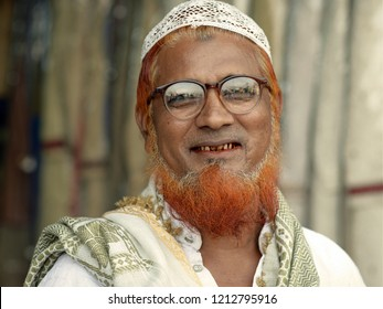 DELHI, INDIA - OCT 19, 2018: Elderly Indian Muslim man with red henna-dyed Islamic beard and betel-stained teeth wears a white Islamic skullcap (taqiya) and smiles for the camera, on Oct 19, 2018.