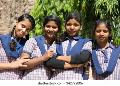 DELHI, INDIA - OCTOBER 11, 2015: unidentified local school girls for tour in Qutub Minar complex, Delhi, India, as part of national education. The girls in school uniform have fun posing for a foto.