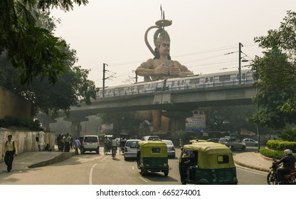 DELHI, INDIA - OCTOBER 20, 2011: Hindu God, Hanuman, towers over the modern metro, people, and traffic belching noxious fumes on October 20, 2011 in Karol Bagh, Delhi, India.