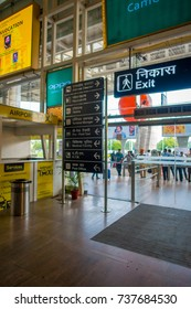 DELHI, INDIA - SEPTEMBER 19, 2017: Informative sign in the exit of the International Airport of Delhi and crowd, Indira Gandhi International Airport is the 32th busiest in the world