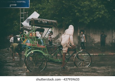 Delhi, India - September 21, 2015: Indian rickshaw rides down the street on the water after a heavy rain. Heavy rain in India in Delhi