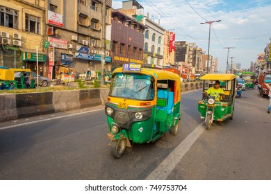 DELHI, INDIA - SEPTEMBER 25 2017: Unidentified people inside of a green motorcycles in the avenue in Paharganj, Delhi. Delhi is the 2nd most populous city in India after Mumbai