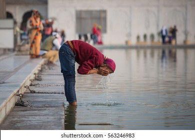 DELHI - JAN 2: Indian devotee washes his face at Gurudwara Bangla Sahib on January 2, 2017 in Delhi, India. This place is one of the most sacred Sikh gurudwara in India and was built in 1783.