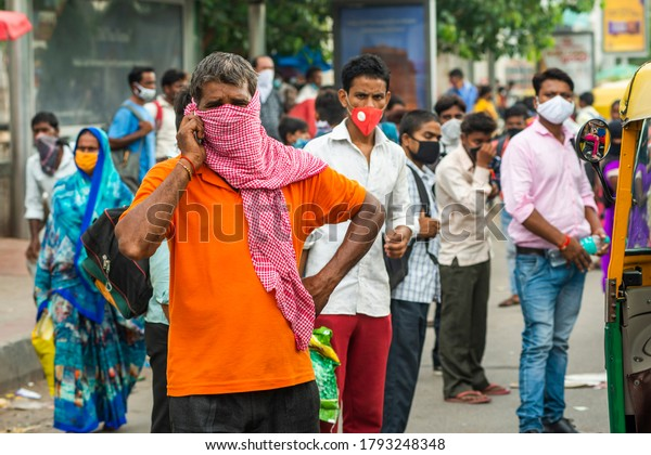 Delhi Uttar Pradesh Border, Delhi/India - Aug 8 2020: Migrants with mask carrying luggage with their families are coming back to city search of work , Migrant from Bihar and Uttar Pradesh .
