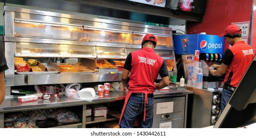 Delhi/India- 06 21 19: one boy serving chicken and other pouring Pepsi in a KFC outlet. serving junk food in a KFC outlet
