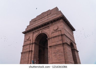 Delhi/India - June 2018: Side profile view of India Gate with birds flying in background