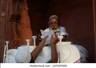 Delhi/India - May,23th,2018 : A man puts ice cubes into the drinking water tank on a hot summer noon during the the month of Ramadan at Jama Masjid in Delhi, India.