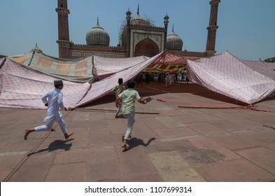 Delhi/India - May,25th,2018 : Boys run to recite the Jummah Namaz (Friday prayer), while the temporary tent collapsed after a strong wind storm right before the prayer at Jama Masjid in Delhi, India.