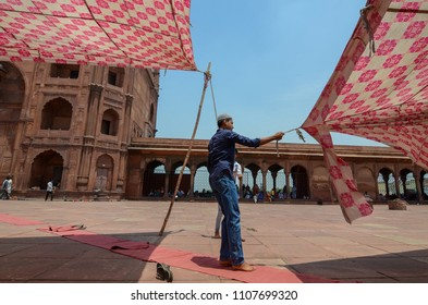 Delhi/India - May,25th,2018 :  A man trying to fix the fallen tent, which collapsed after a wind storm right before the Friday noon prayer in Jama Masjid.