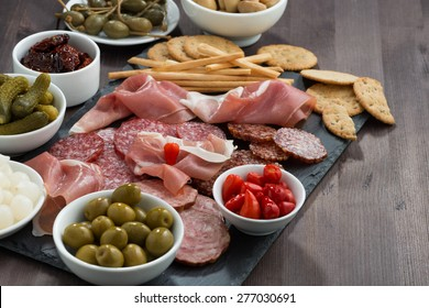 deli meat snacks, sausages and pickles on a dark wooden table, horizontal