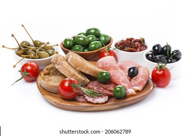 deli meats, pickles and olives on a wooden board, isolated on white